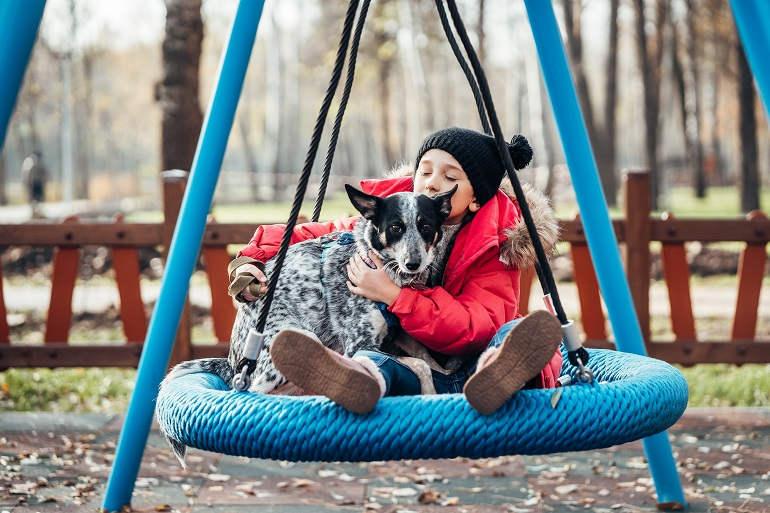 Mädchen mit Hund auf Schaukel